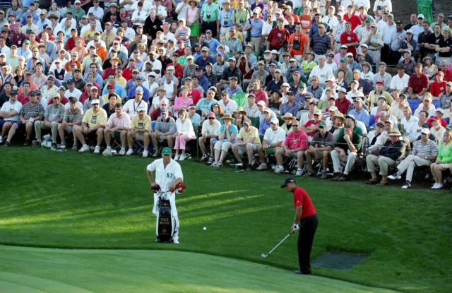 Tiger Woods chips a shot to the 16th green for birdie as his caddie, Steve Williams, looks on during the final round of The Masters at the Augusta National Golf Club on April 10, 2005 in Augusta, Georgia. Thegallery watches on as Tiger Woods' ball is airbourne just after he makes contact witht he ball.