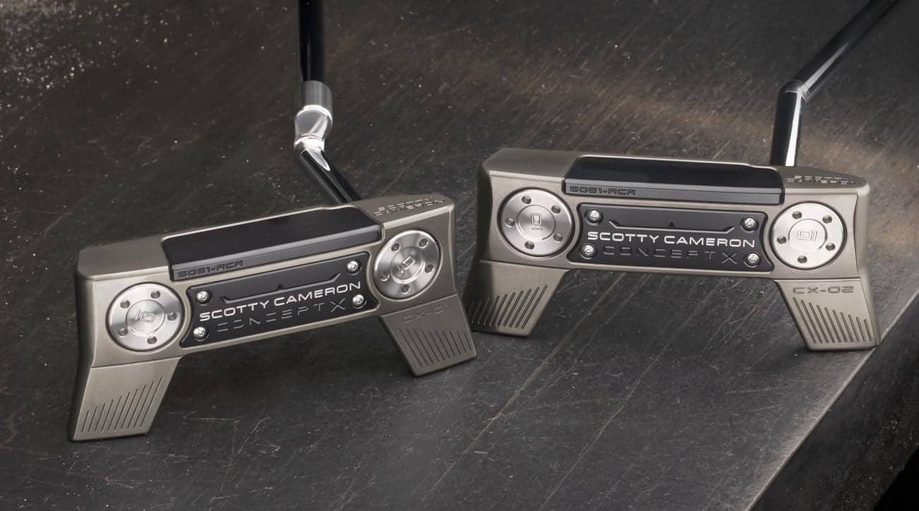 A pair of Scotty Cameron Concept X Putters laying down so you can see the bottom of each putter