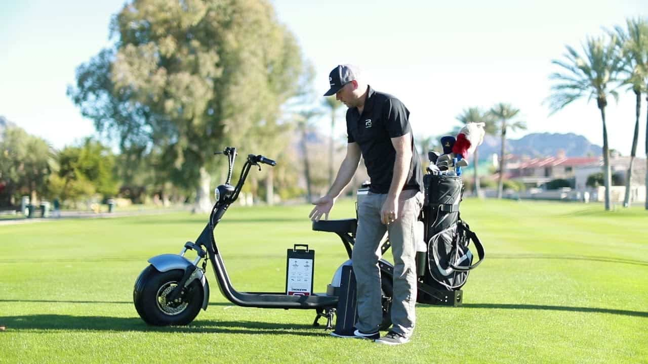 Man wearing a black polo shirt and a black golf hat presenting a Phat Golf Scooter with a golf bag on the back in a golf course setting.