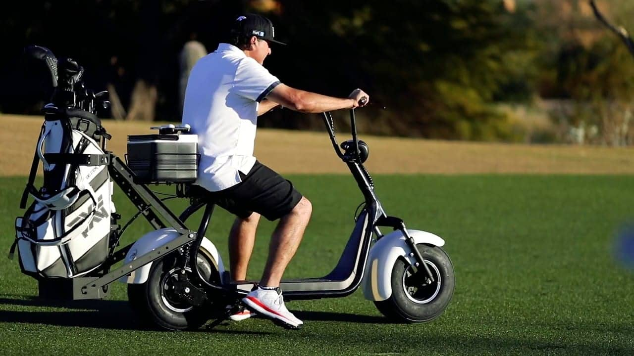 Pat Perez Driving a Phat Golf Scooter wearing an untucked white polo shirt and a black hat. On the golf course with a golf bag attached on the back of the electric scooter