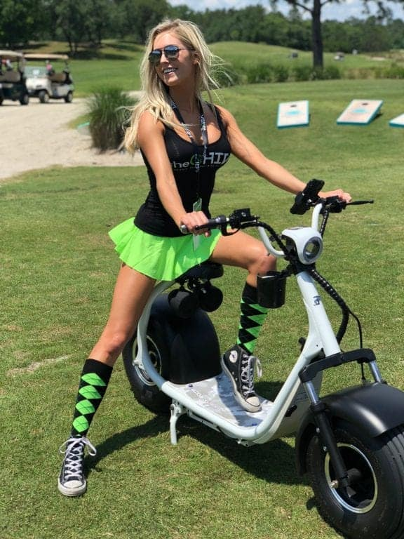 Blonde girl wearing a chive shirt and bright green skirt riding a phat golf scooter on a fairway