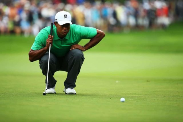 Tiger Woods circa 2013 wearing a aqua green polo and white tiger woods brand nike hat eyeing up a long putt
