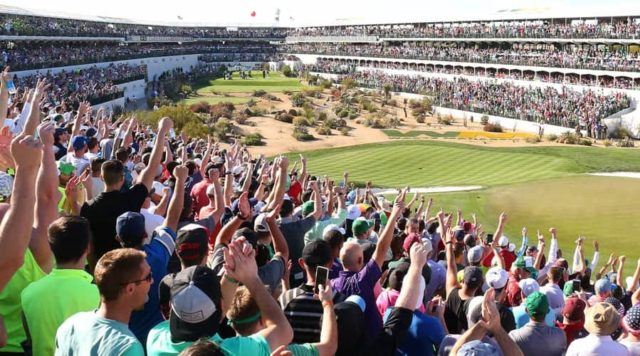 Crowd cheering with hands in air at a unique stadium like setting at the 16th hole of the waste management open in Phoenix, Arizona