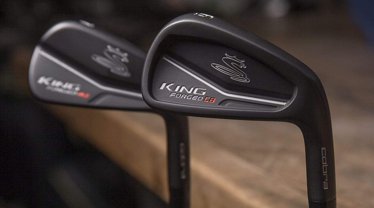 2 cobra King Forged CB Irons in matte black with cobra logo. Groove on clubface facing away from camera.