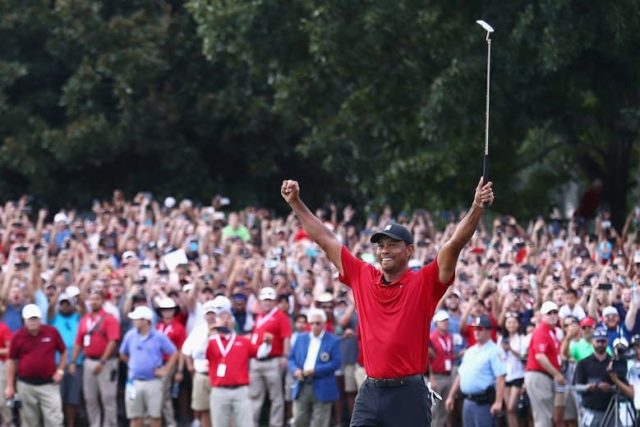Tiger Woods holds his putter in the air to celebrate his victory at the 2018 Tour Championship