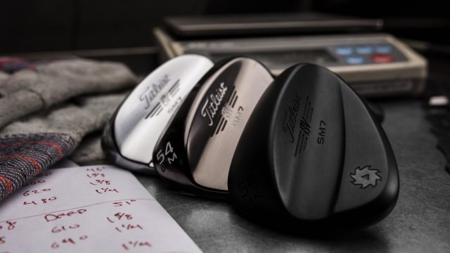 3 Titleist Vokey SM7 Wedges without a shaft sitting atop a work bench staggered. Jet Black, brushed steel, and tour chrome finish pictured.