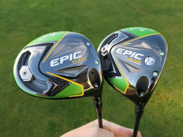 Two Golf Club Heads held up by a human hand. On the left is a Callaway Epic Flash Driver and on the right is Callaway Epic Flash Fairway Wood. Both Clubs are new for 2019. Both are Black, Green, with yellow accents. The text Epic can be seen in white writing on both clubs.