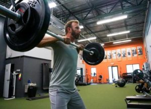 Dustin Johnson lifting a barbell and performing an upright barbell row. Dustin Johnson Workout