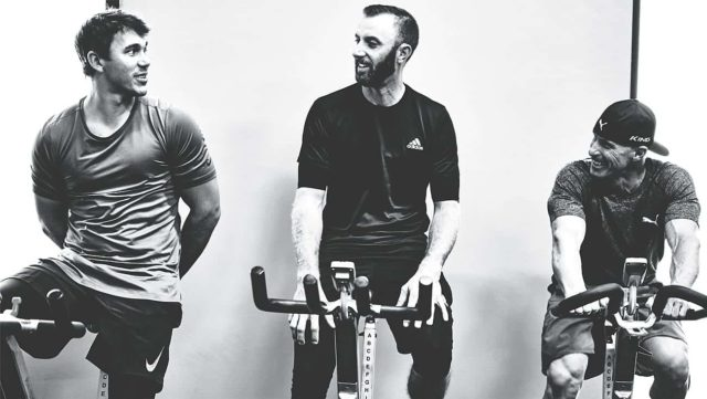 Dustin Johnson and Brooks Koepka spin cycling next to Joey D at he Joey D Golf Fitness Center