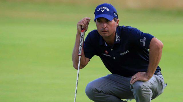 Kevin Kisner eyeing up a putt wearing dark blue polo shirt, grey pants, and a royal blue callaway golf hat