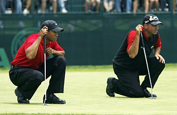 Rocce Mediate and Tiger woods both lined up looking at putts. Rocco Mediate wearing Tiger's Traditional Attire which is red shirt and black pants before they begin the 18-hole playoff at Torrey pines.