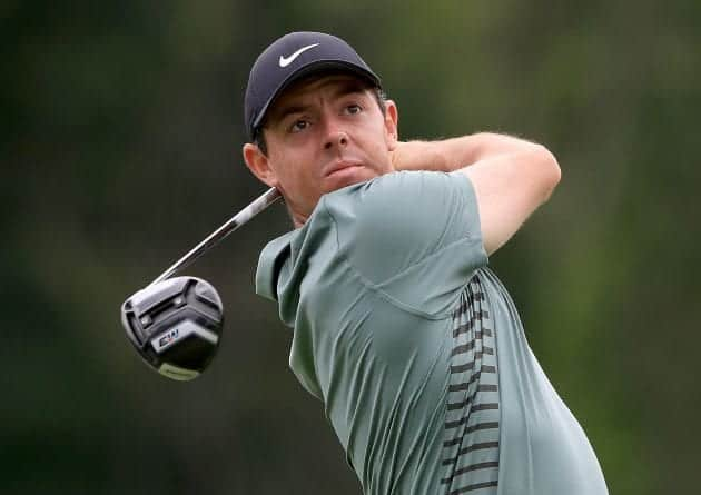 Rory McIlroy swinging his TaylorMade M3 Driver wearing green polo and black Nike hat