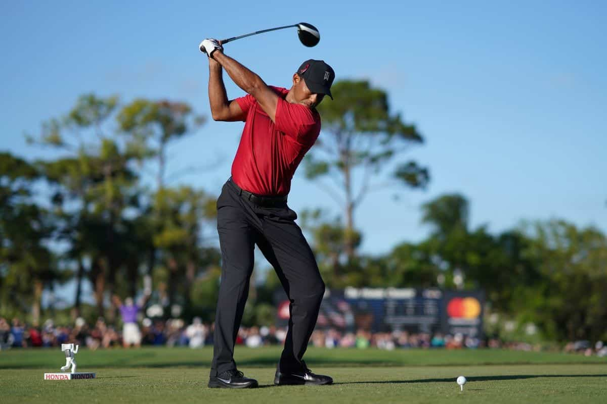 Tiger Woods Teeing off wearing red shirt and black pants with a black hat. At the top of his back swing