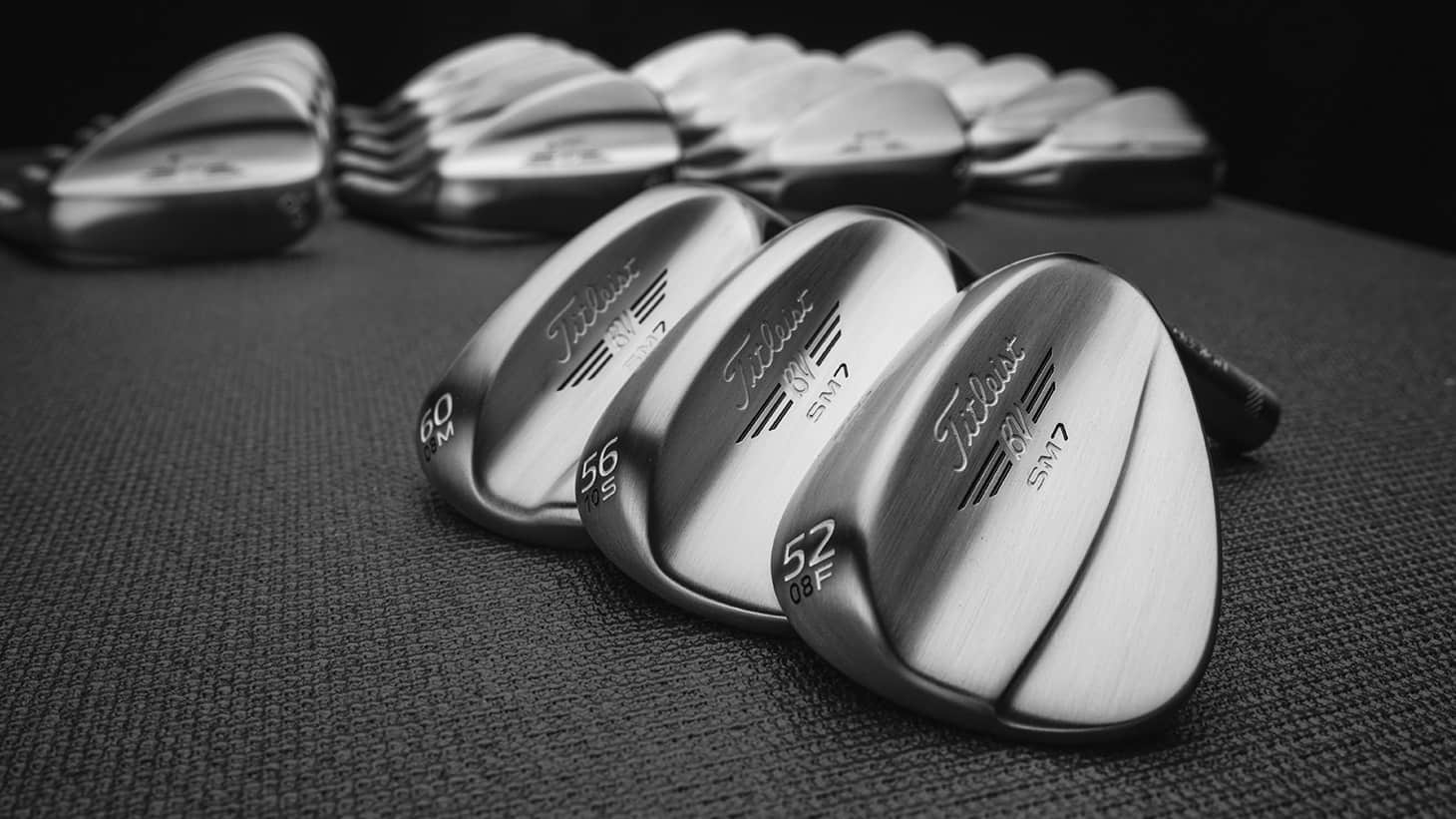 3 Titleist Vokey SM7 Wedges in Raw finish in foreground with several more in out of focus background.
