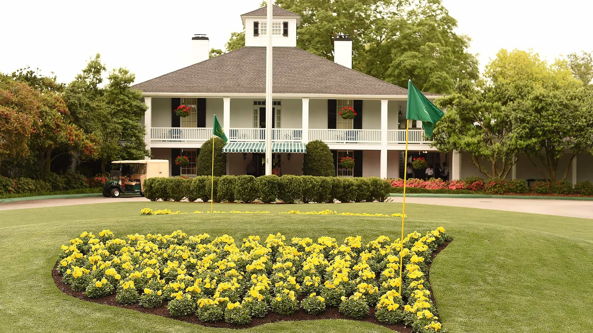 A view of the clubhose at augusta national golf club house with the united states shaped yellow flowers in front.