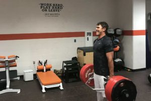 Brooks Koepka doing a deadlift with a hex bar in a gym. Brooks Koepka Workout