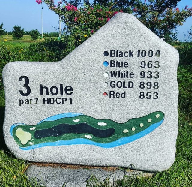 Stone tablet yardage marker for the par-7 3rd hole at gunsan country club in south korea