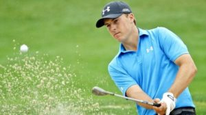 Jordan Spieth hits a bunker shot with sand rising out of the trap