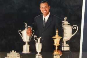 Tiger Woods posing in front of his 4 trophies after winning the 2000 US Open, British Open, PGA Championship, and 2001 Masters.