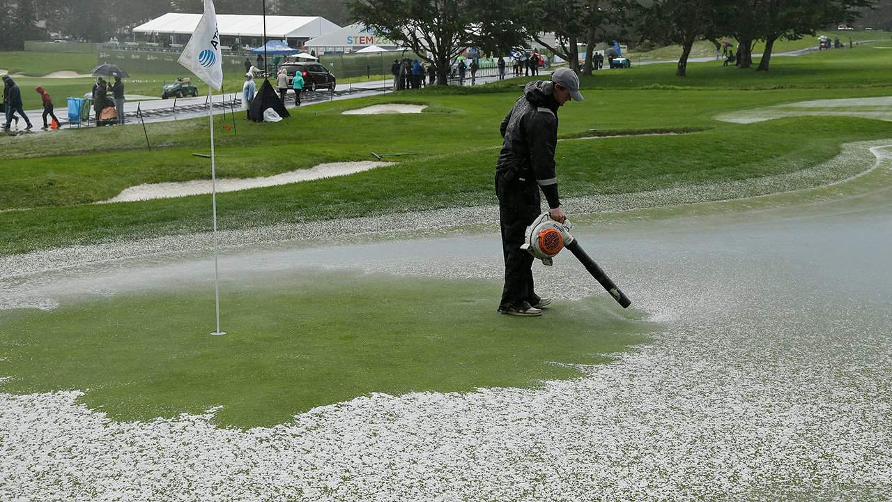 2019 Pebble Beach Pro-Am grounds keepers use leaf blowers to clear the greens off from hail and ice