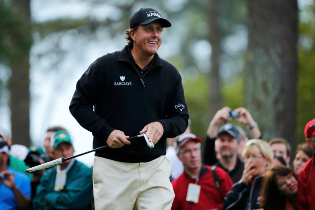 Phil Mickelson Cleaning off his golf club with a big smile as he walks by the gallery at the 2004 Masters tournament at Augusta National