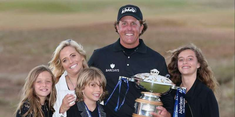 Phil Mickelson poses for a picture after winning an event with his wife Amy and his 3 children