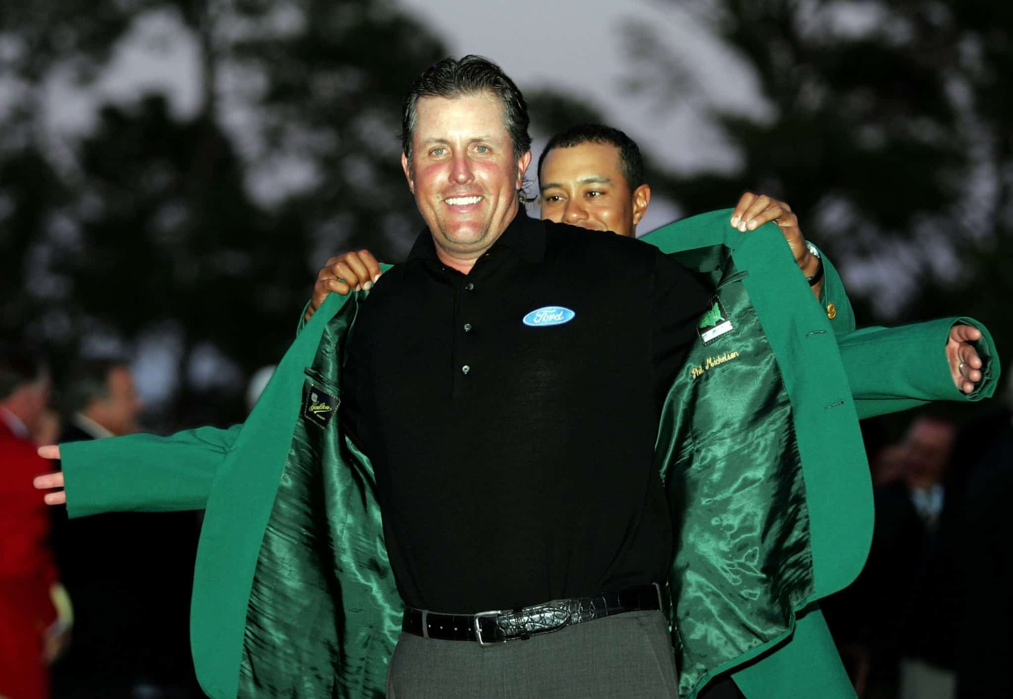 Phil Mickelson recieves the green jacket after winning the 2006 masters. Tiger Woods the 2005 winner is the person placing the green jacket on Mickelson
