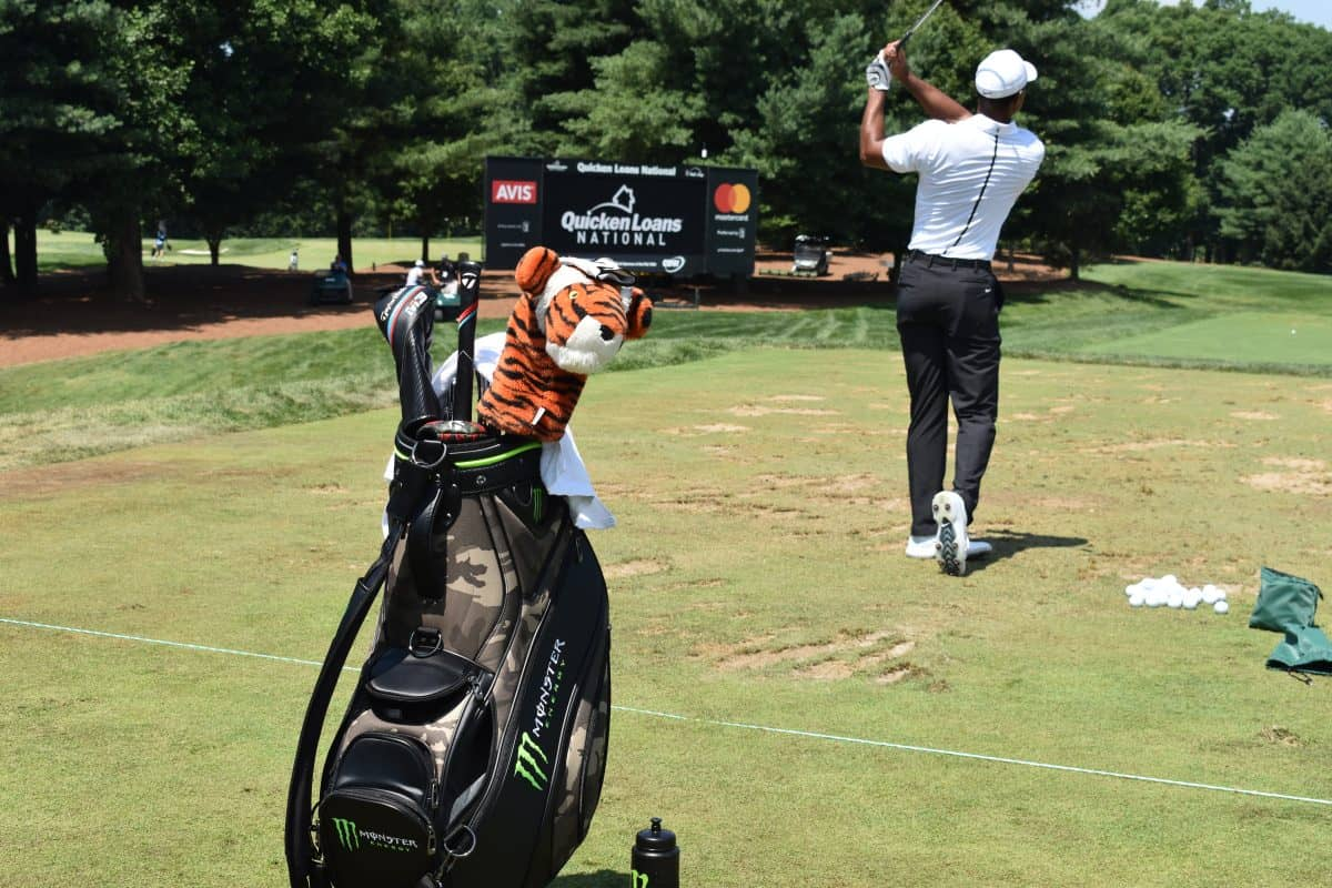 Tiger Woods hitting golf balls on the range wearing a white polo shirt with his Black monster energy golf bag for 2019 behind him with the tiger head cover facing the camera.