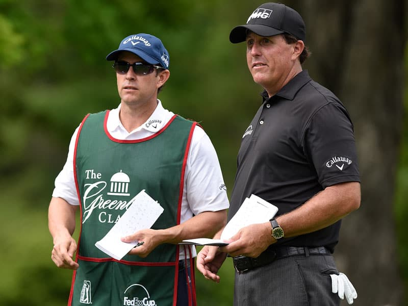 Phil Mickelson standing next to his caddie, and brother, Tim Mickelson. Both are looking on at play during a tournament
