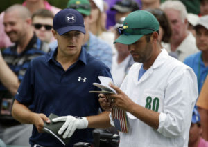 Jordan Spieth talking with his caddie, Michael Greller at the Masters tournament.