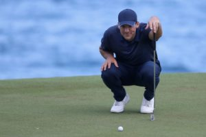 Tony Romo eyeing up a putt on a green
