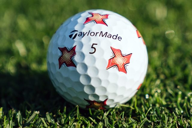 TaylorMade PIX TP5 Golf Balls with Ninja Star Design sitting on the grass with the TaylorMade Logo facing forwards and upwards.