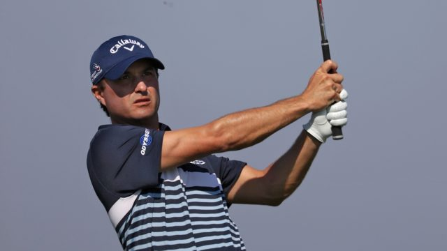 Kevin Kisner finishes his swing and stares down his iron shot while wearing a blue callaway golf hat. Kevin Kisner Money
