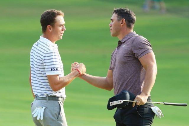 Justin Thomas and Brooks Koepka shaking hands after a round of golf on the green