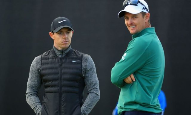 Justin Rose and Rory McIlroy standing around and talking during a round of golf