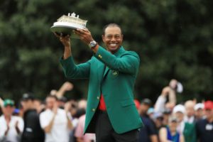 Tiger wearing his green jacket hold up the Masters trophy after winning the 2019 tournament