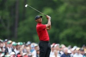 Tiger swinging his golf club at the 2019 Masters Tournament, wearing his classic red shirt and black at on Sunday