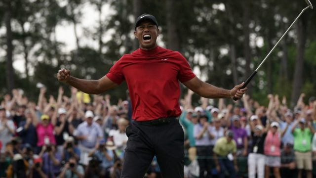 Tiger Woods celebrates on the 18th green during the Masters Tournament at Augusta National Golf Club