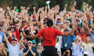 Patrons cheer as Tiger Woods Masters Champion of the United States celebrates after sinking his putt on the 18th green to win during the final round of the Masters at Augusta National Golf Club.