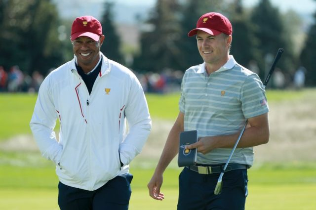 Tiger Woods and Jordan Spieth joke with one another with their matching red hats at the 2018 Ryder Cup