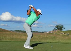 Brooks Koepka in a green shirt swinging a golf club from a tee box