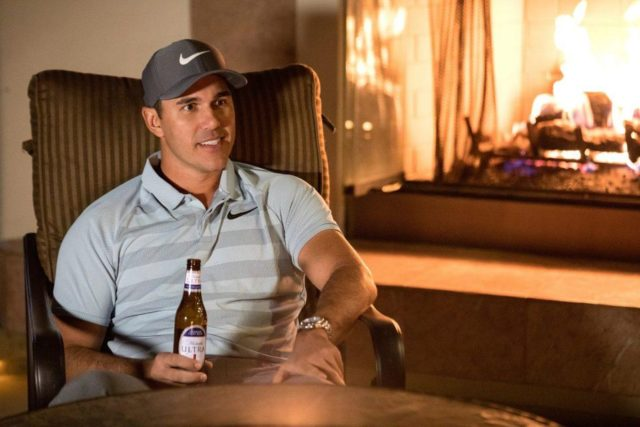 Brooks Koepka drinks a Michelob Ultra while wearing Nike golf apparel