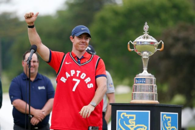 Rory McIlroy wins Canadian Open 2019. Rory celebrates with the trophy wearing a toronto raptors kyle lowry jersey ahead of teh 2019 NBA Finals